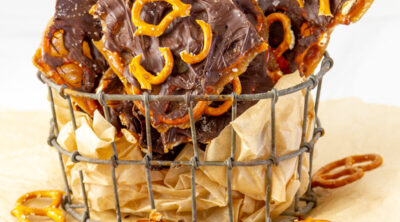 square crop of pieces of bark in a wire container with a piece in front and some broken pretzels around