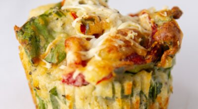 square crop of savory spinach muffin topped with cheese