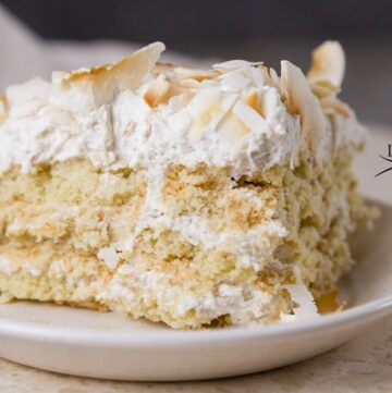 Looking for a quick and easy dessert recipe? Try my delicious Toasted Coconut Ice Box Cake. Just whip up some coconut whipped cream, layer it on coconut cookies, and top it with beautiful coconut chips. The hardest part is waiting for it to set up in the fridge.