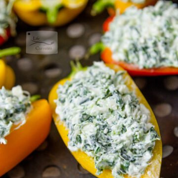 Grilled Cheesy Spinach Dip Stuffed Peppers peppers stuffed with spinach dip on a grill tray ready to be cooked