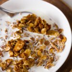 Homemade Granola Recipe served with milk in a white bowl