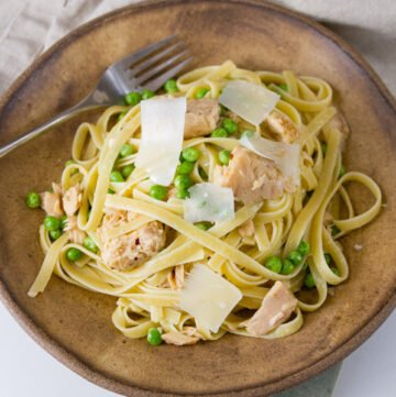 Easy Weeknight Tuna Pasta Dinner in a brown bowl with a fork topped with Parmesan