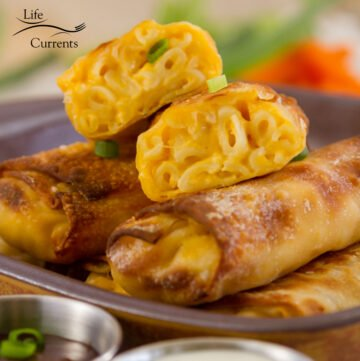 square crop of Mac and Cheese Egg Rolls on a serving plate garnished with green onions