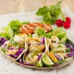 square crop of Shrimp Tacos with Roasted Garlic Sauce on a plate with a side salad, radishes in the background