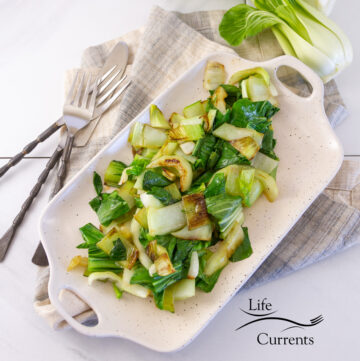 square crop of cooked bok choy on a platter with silverware and a fresh head of bok choy.