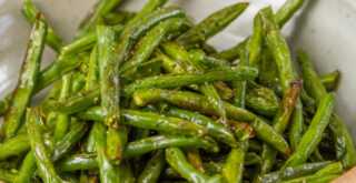 cooked green beans in a ceramic bowl, cropped square image
